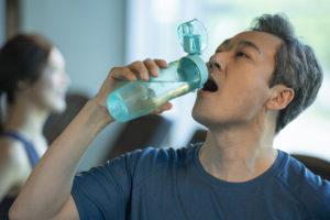 ボトルに水素水を入れている男性
