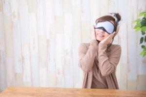 ホットアイマスクで目の疲れを取る女性