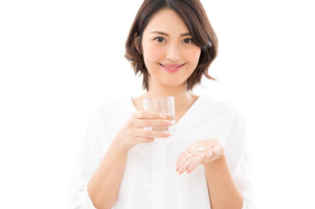 女性用サプリメントを飲む女性